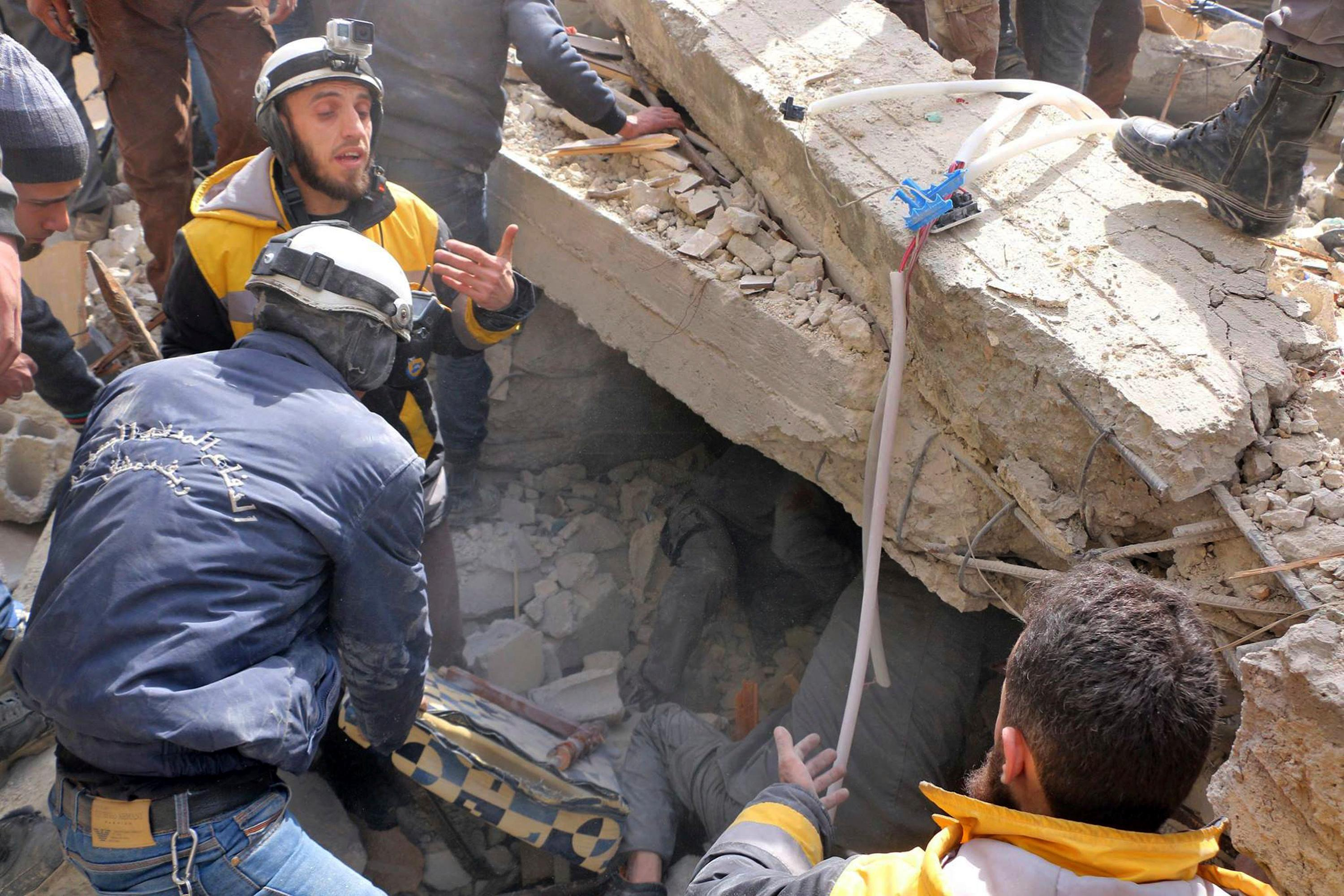 This photo provided by the Syrian Civil Defense group known as the White Helmets, shows Civil Defense workers digging for survivors underneath a damaged building after airstrikes hit a rebel-held suburb near Damascus, Syria, Monday, Feb. 5, 2018. Syrian opposition activists said more than one dozen people killed in new airstrikes. (Syrian Civil Defense White Helmets via AP)