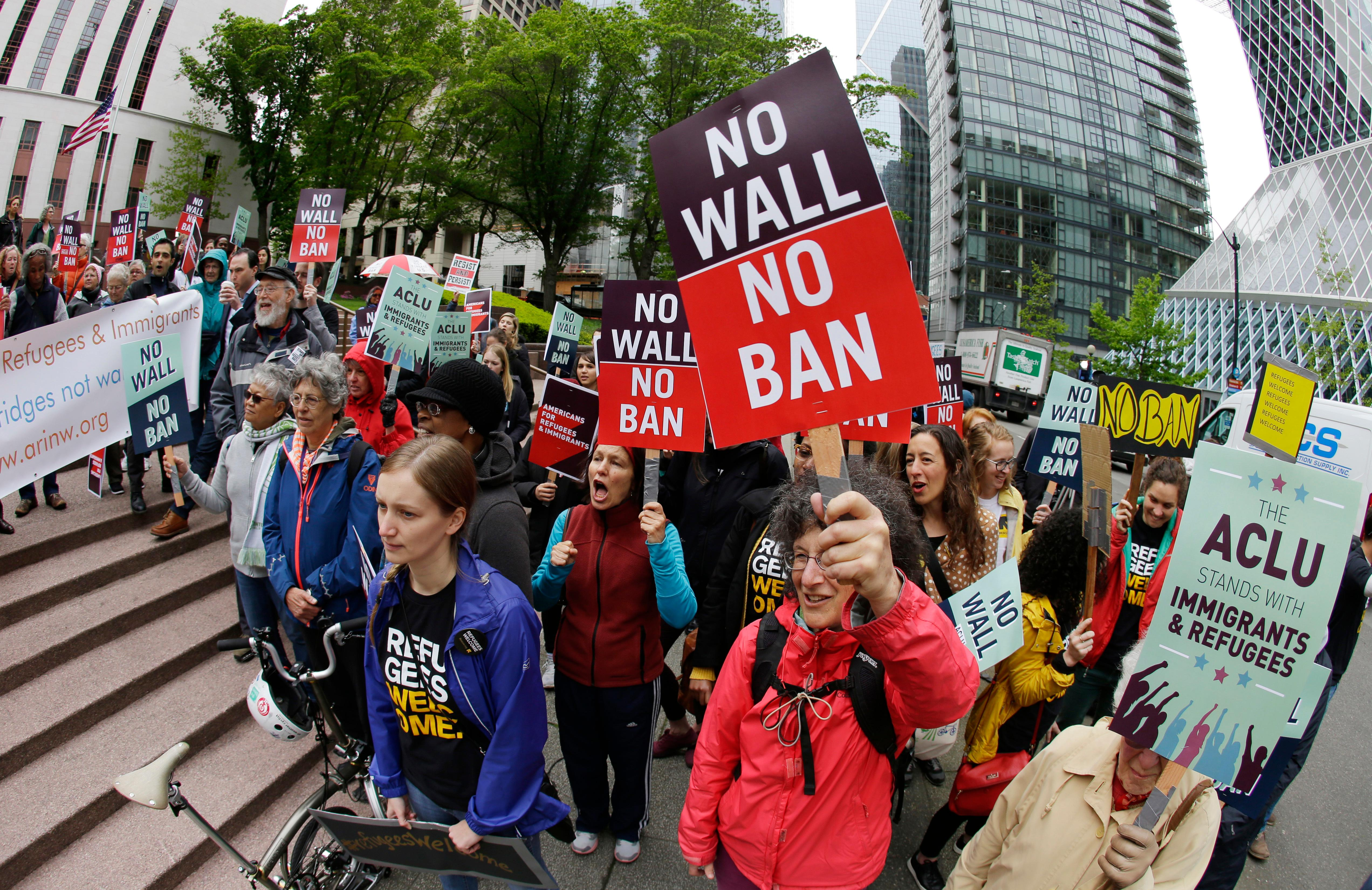 FILE - In this May 15, 2017 file photo, protesters wave signs and chant during a demonstration against President Donald Trump's revised travel ban outside a federal courthouse in Seattle. (AP Photo/Ted S. Warren, File)