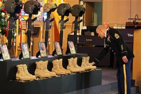 First Sgt. Daniel Sutczak leaves a coin at a memorial for five soldiers killed in Afghanistan during a chapel service Thursday, January 09, 2014, at Fort Riley, Kan. The five were killed in December when their helicopter crashed on a mission.