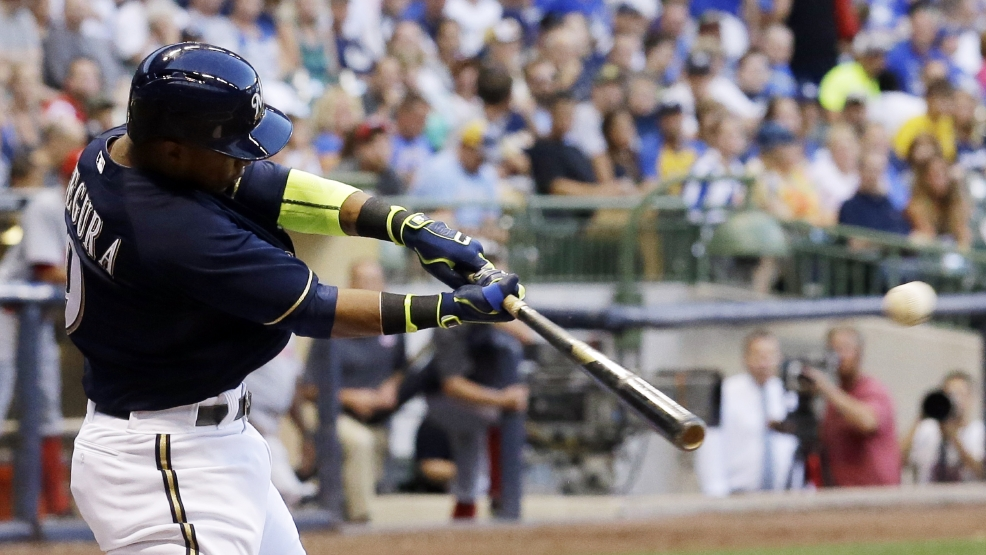 Milwaukee Brewers' Jean Segura hits a triple during the third inning of a baseball game against the Cincinnati Reds Monday, July 21, 2014, in Milwaukee. Segura scored on a throwing error. (AP Photo/Morry Gash)
