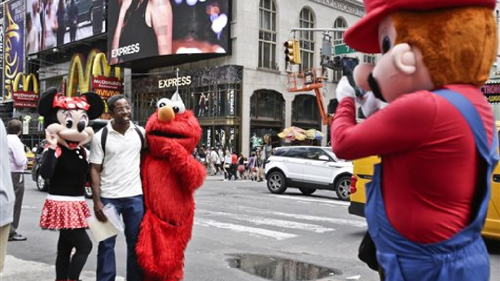 A visitor to Times Square poses for photos with iconic costumed characters, Monday, July 28, 2014, in New York. New York Mayor Bill de Blasio said Monday that he believes the people wearing character costumes in Times Square should be licensed and regulated. (AP Photo/Rachelle Blidner)