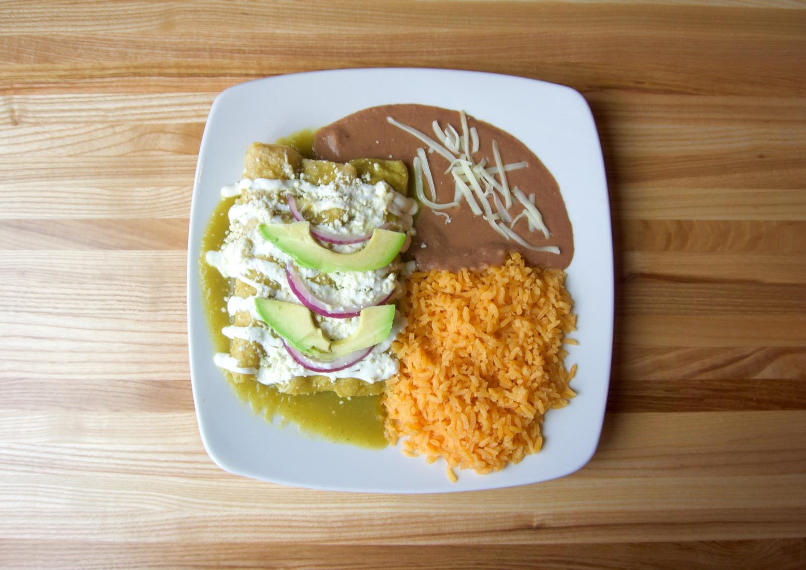 <p>Chicken enchiladas: three corn tortillas with chicken topped with green, red, or cheese sauce, sour cream, feta cheese, and red onion, served with rice and beans / Image: Brian Planalp // Published: 1.29.18</p>