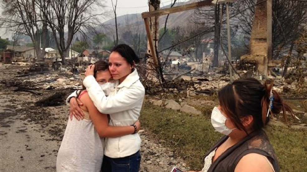 Emma Franco, center, is consoled after she lost her mobile home in the town of Pateros, Wash., on Friday, July 18, 2014. Authorities say the wildfire has already burned about 100 homes and prompted the evacuation of Pateros, home to about 650 people in Okanogan County. A hospital in nearby Brewster was also evacuated as a precaution. (AP Photo/The Seattle Times, Mike Siegel)
