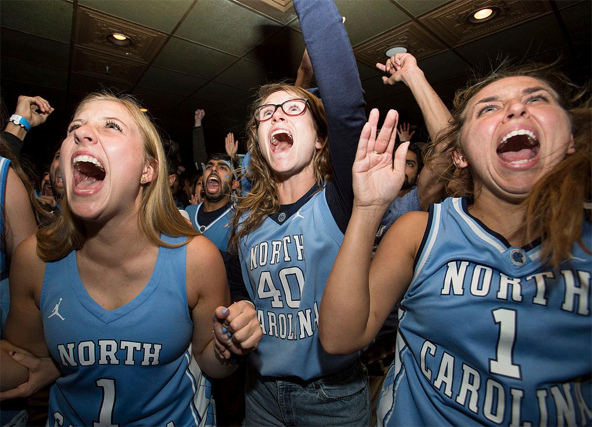Maribeth Bloncheck, from left, Adeline Dorough, and Liza Kate Wall celebrate at a restaurant as North Carolina defeated Gonzaga to win the NCAA college basketball championship in Chapel Hill, N.C., Monday, April 3, 2017. (AP Photo/Ben McKeown)