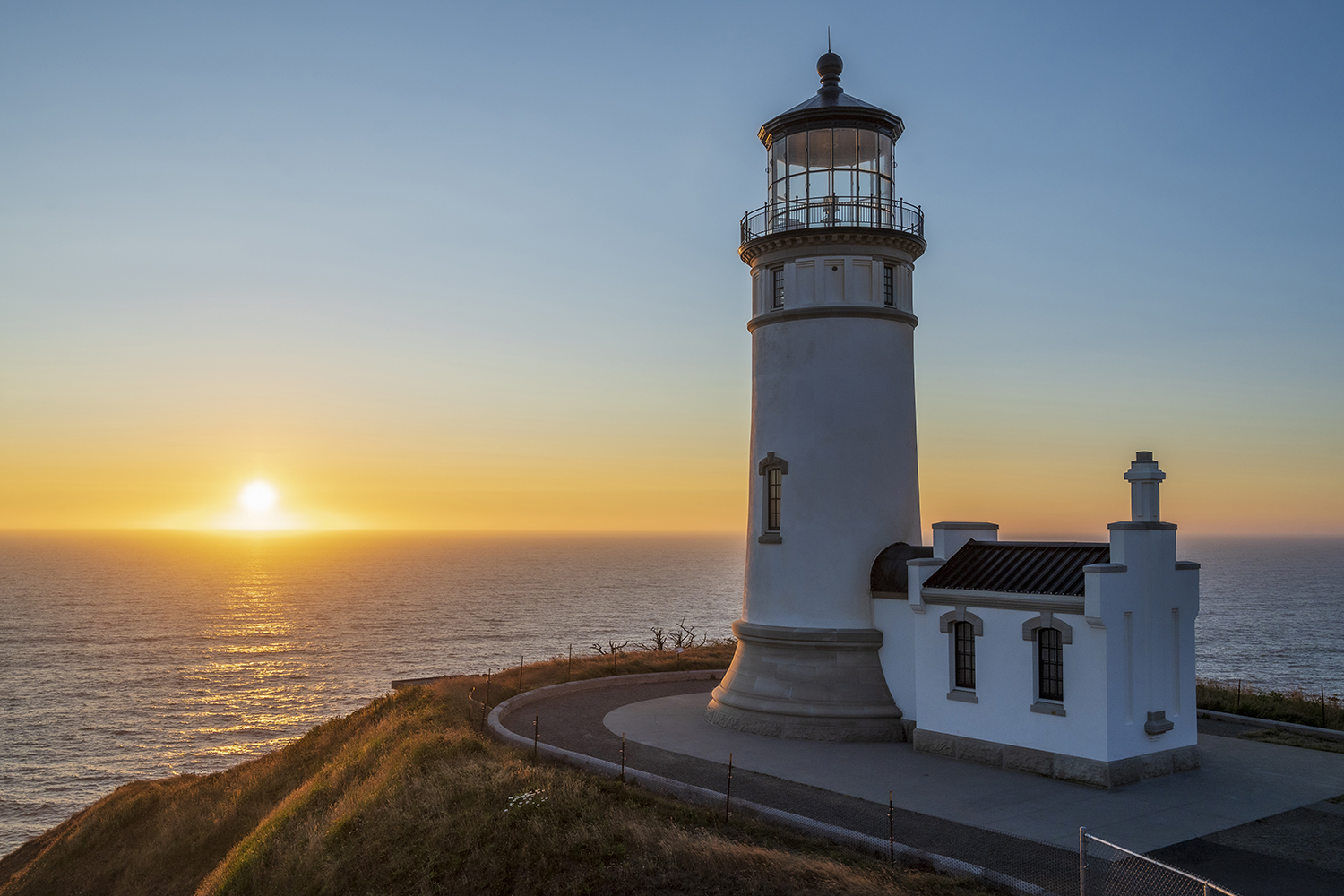 "Cape Disappointment State Park features two ""postcard picture"" lighthouses: Cape Disappointment Lighthouse and North Head Lighthouse. Seen here at sunset, the century-old North Head Lighthouse is about a six-minute drive from Cape Disappointment Lighthouse located inside the state park and guides marine traffic approaching from the north.{ }(Image: Rachael Jones / Seattle Refined)"