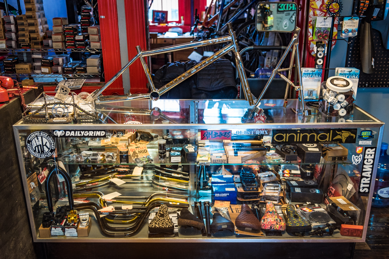 At the back of the shop is a glass case filled with an assortment of bike accessories. An original 1993 S&M dirt bike frame sits atop the case. / Image: Phil Armstrong, Cincinnati Refined // Published: 3.19.17