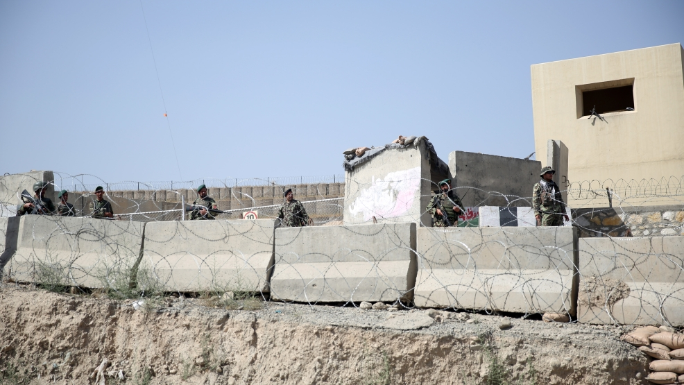 Afghanistan National Army soldiers stand guard at a gate to Camp Qargha, west of Kabul, Afghanistan, Tuesday, Aug. 5, 2014. (AP Photo/Massoud Hossaini)