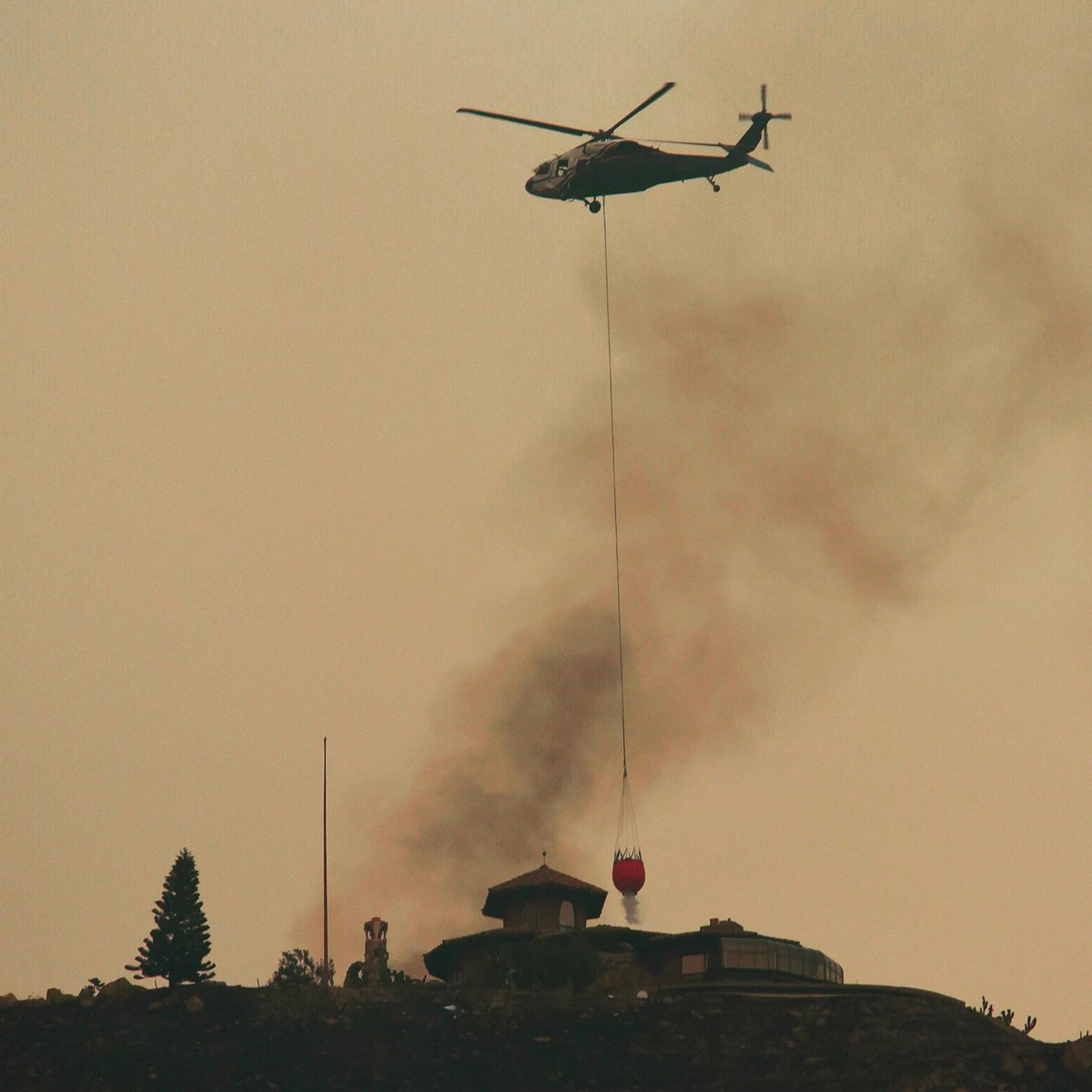 In this photo provided by the Santa Barbara County Fire Department, a helicopter makes water drop near a house that was not on fire on a hill above Bella Vista Drive in Montecito, Calif., as the fight to contain a wildfire continues Tuesday, Dec. 12, 2017. The fifth-largest wildfire in California history expanded Tuesday, ripping through dry brush atop a coastal ridge while crews struggled to keep flames from roaring down into neighborhoods amid fears of renewed winds. (Mike Eliason/Santa Barbara County Fire Department via AP)