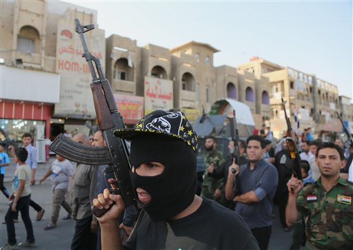 Shiite tribal fighters raise their weapons and chant slogans against the al-Qaida-inspired Islamic State of Iraq and the Levant (ISIL) in the northwest Baghdad's Shula neighborhood, Iraq.