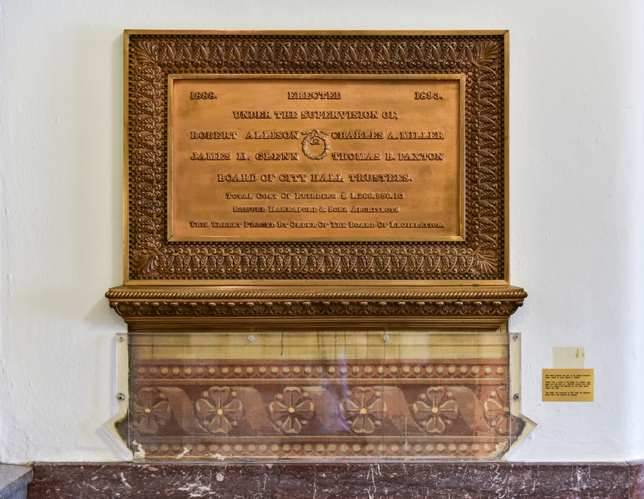 A plaque detailing the history of those officials responsible for the building's erection sits on the wall near the Plum Street entrance. Below it, a preserved piece of the original building's wall design is protected under plexiglass. / Image: Phil Armstrong, Cincinnati Refined // Published: 1.20.17