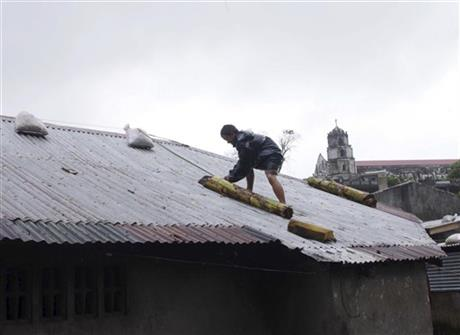 A man reinforces his house with banana stalks as powerful typhoon Haiyan hits Legazpi city, Albay province