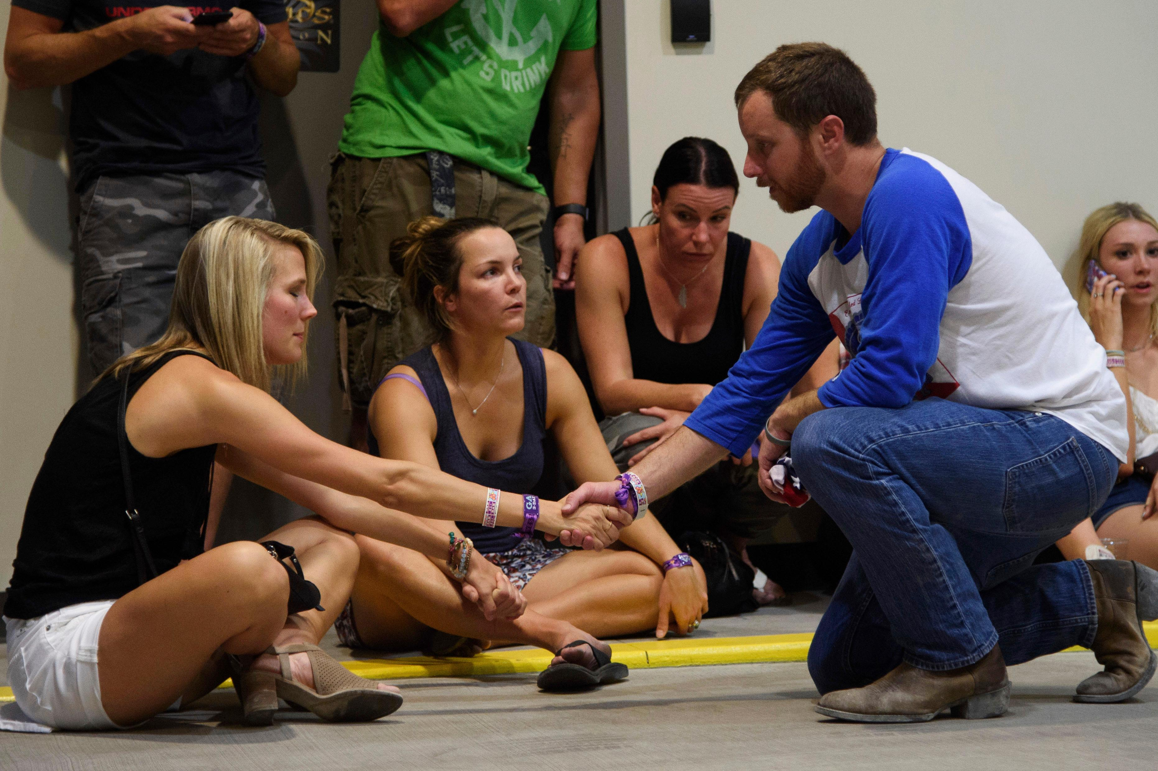People hold hands in prayer while hiding inside the Sands Corporation plane hangar after a mass shooting in which dozens were killed at the Route 91 Harvest Festival on Sunday, Oct. 1, 2017, in Las Vegas. (Al Powers/Invision/AP)