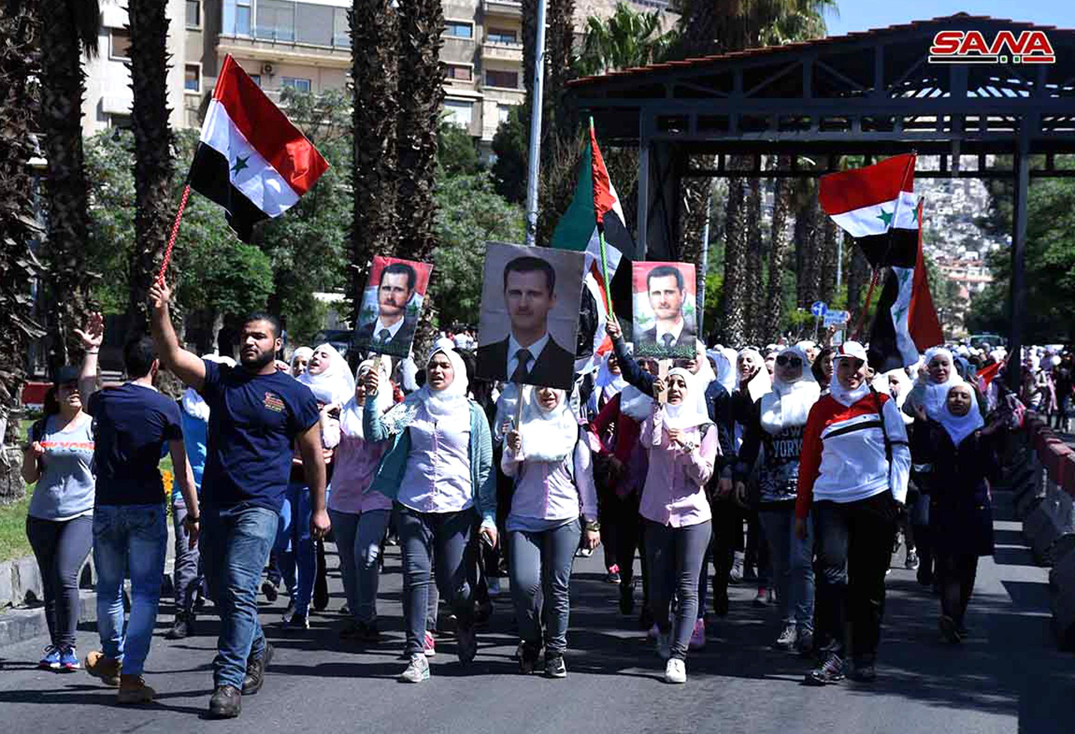 In this photo released by the Syrian official news agency SANA, Syrian protesters hold their national flags and portraits of their president Bashar Assad, as they march during a demonstration to show their solidarity with the Syrian armed forces, at Omayyad Square, in Damascus, Syria, Monday, April 16, 2018. Hundreds of Syrians have gathered in a landmark square in the capital of Damascus in support of their armed forces, which they say succeeded in confronting the unprecedented joint airstrikes by the West over the weekend. (SANA via AP)