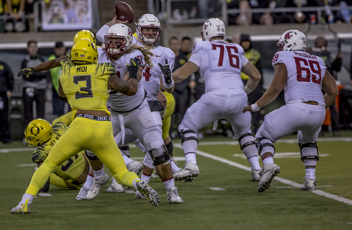 Washington  State quarterback Luke Falk (#4) looks to make a pass amidst a group of defenders. The Oregon Ducks trail the Washington State Cougars 10 to 13 at the end of the first half. Photo by Ben Lonergan, Oregon News Lab