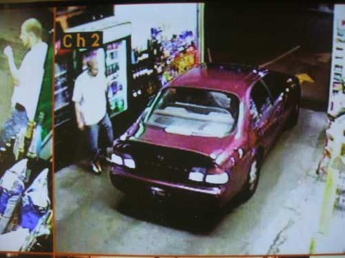 Surveillance images show a red getaway car during a robbery of the Brew Thru Beverage store