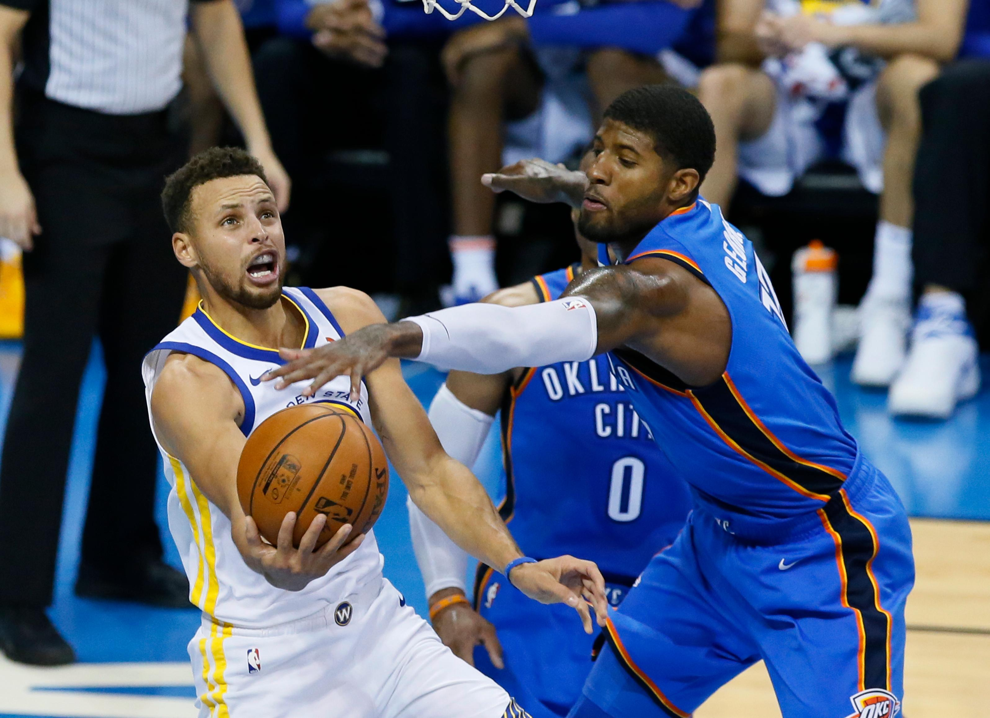 Golden State Warriors guard Stephen Curry, left, shoots as Oklahoma City Thunder forward Paul George, right, defends, during the second quarter of an NBA basketball game in Oklahoma City, Wednesday, Nov. 22, 2017. (AP Photo/Sue Ogrocki)