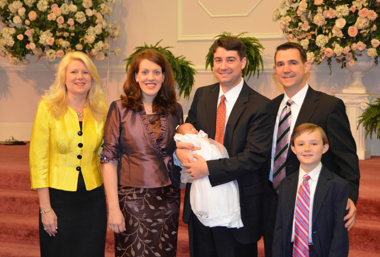 FILE - In this 2012 photo provided by a former member of the church, Jeffrey Cooper holds his infant daughter at her 2012 baby dedication at the Word of Faith Fellowship compound in Spindale, N.C. At second right is Frank Webster, an assistant North Carolina prosecutor who is married to church leader Jane Whaley's daughter, Robin, left. At right is Frank Webster's son, Brock. At second left is Jeffrey Coopers' wife, Natalie. A district attorney has asked the state to investigate two assistant prosecutors after an Associated Press story that quoted former congregants of a North Carolina church as saying the men derailed criminal probes into allegations of abuse by sect leaders. The AP story, released Monday, March 6, 2017, cited nine former Word of Faith members who said Frank Webster and Chris Back provided legal advice, helped at strategy sessions and participated in a mock trial for four congregants charged with harassing a former member. (AP Photo, File)