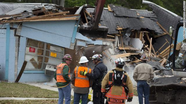 Workers watch the demolition of the house where a sinkhole opened beneath the bedroom of Jeff Bush three days before in Seffner, Florida, on Sunday, March 3.